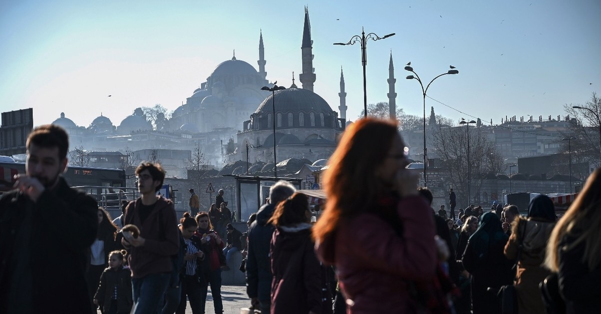 People walk in Istabul's Eminu00f6nu00fc district in front of the Rustem Pau015fa (front) and Su00fcleymaniye (back) mosques, Feb. 19, 2019.