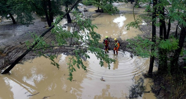 Rescuers stand in a flooded camping site, Saint-Julien-de-Peyrolas, Aug. 9.