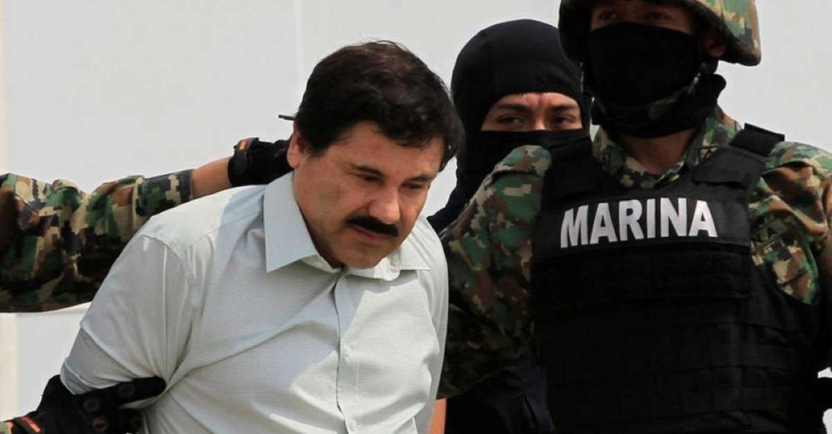 Joaquin ,El Chapo, Guzman (L) is escorted by soldiers during a presentation at the Navy's airstrip in Mexico City Feb. 22, 2014. (Reuters Photo)