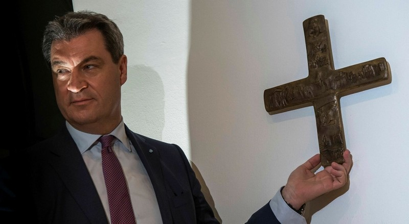 Markus Soeder, Bavarian State Premier, hangs a cross in the entrance area of the Bavarian State Chancellery, Munich, April 24, 2018. (AFP Photo)