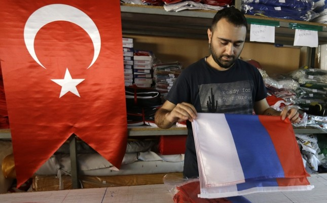 An employee of a flag-making factory folds a Russian flag as a Turkish flag adorns the display at left, in Istanbul, Aug. 9.