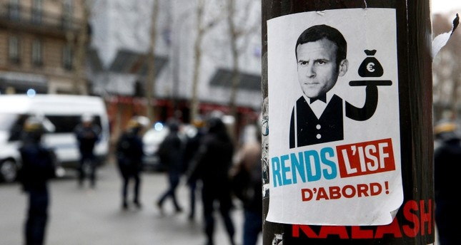 A sticker showing a portrait of French President Emmanuel Macron and the message Reinstall the wealth tax is seen in a street during a national day of protest by the yellow vests movement in Paris, France, December 8, 2018. (Reuters Photo)