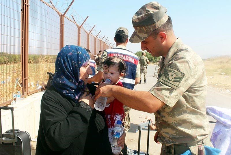 A Turkish gendarmerie officer gives water to a Syrian refugee child preparing to cross the border on Qurban Bayram holidays in August (Sabah File Photo)