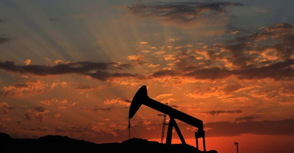 The sun sets behind an oil pump in the desert oil fields of Sakhir, Bahrain. (AP Photo)