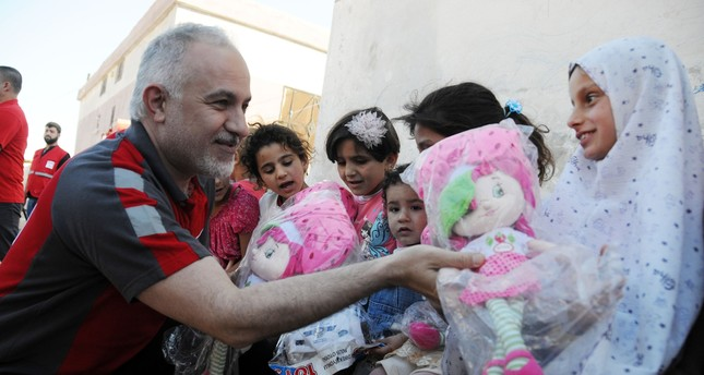 Dr. Kınık gives toy kits to orphaned children in Idlib who lost their parents during the Syrian Civil War, as part of Turkish Red Crescent's humanitarian aid program for the region.