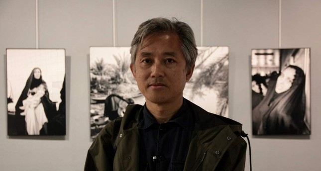 Lam Duc Hien poses in front of his photos at the exhibit.
