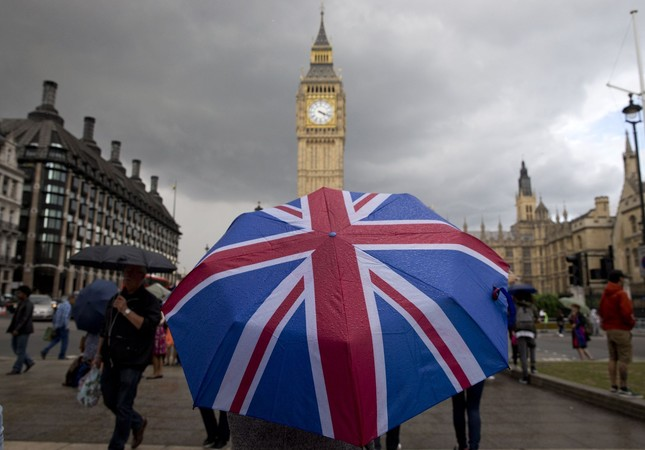 A pedestrian shelters from the rain beneath a Union flag themed umbrella as they walk near the Big Ben clock face and the Elizabeth Tower at the Houses of Parliament in central London on June 25, 2016 (AFP Photo)