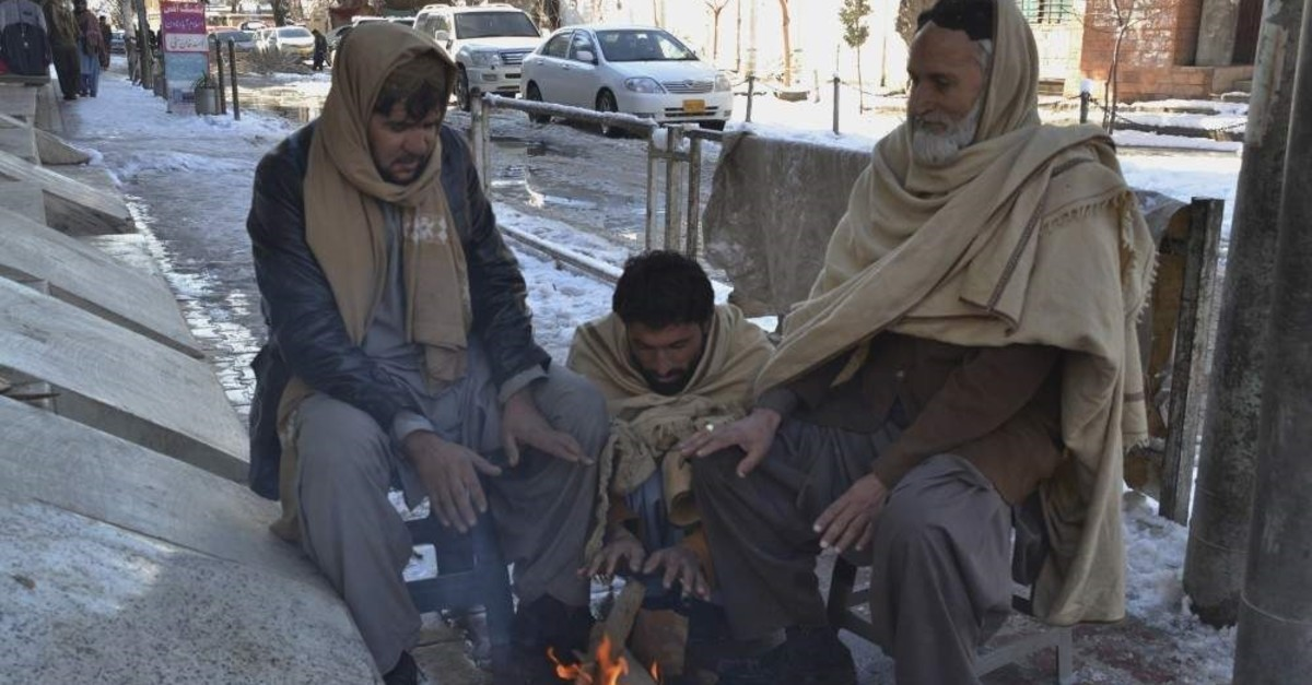 People sit around a fire after heavy snowfall in Quetta, the capital of Pakistan's southwestern Baluchistan province, Jan. 13, 2020. (AP Photo)