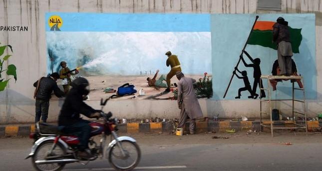 Artists paint graffiti on a bridge wall to show their solidarity with Indian Kashmiri Muslims, Peshawar, Feb. 4, 2020. AFP Photo