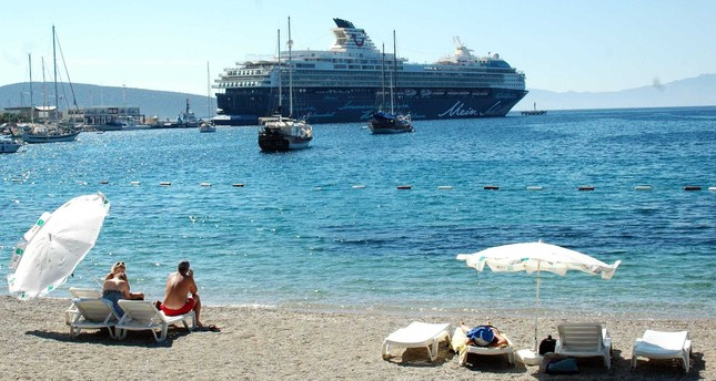 Tourists on the beach watch a cruise liner carrying more than 2,000 tourists in Bodrum, a popular resort in the southwest on Oct.6.