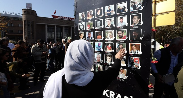 A woman touches the photos of victims during a commemoration ceremony at the scene of attacks, Oct. 10, 2019.