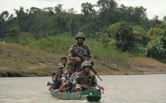 Myanmar Border Guard Police officers travel in a wooden boat at the Tin May village, Myanmar, July 14.