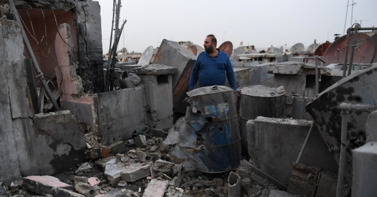 A man stares at the damage on the roof of a building that was hit by a rocket in the northern city of Aleppo, Syria, April 14, 2019. (AFP Photo)