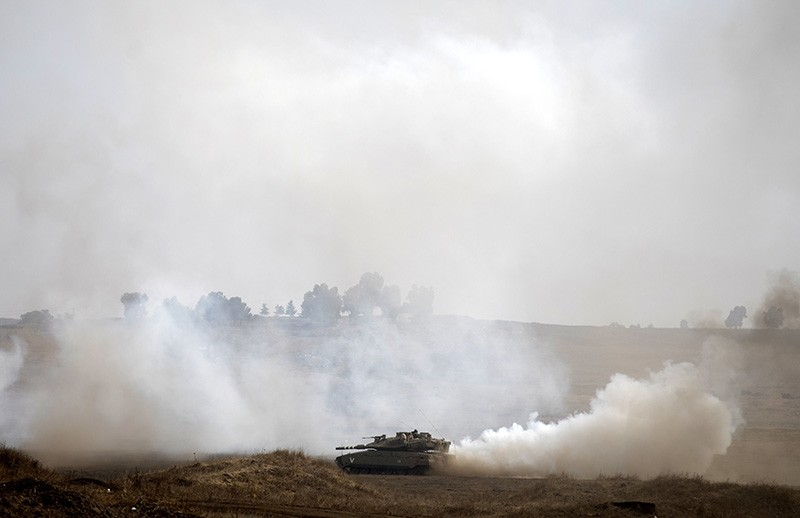 Israeli tanks train at the Golan Heights area, on the Israeli-Syrian border (EPA Photo)