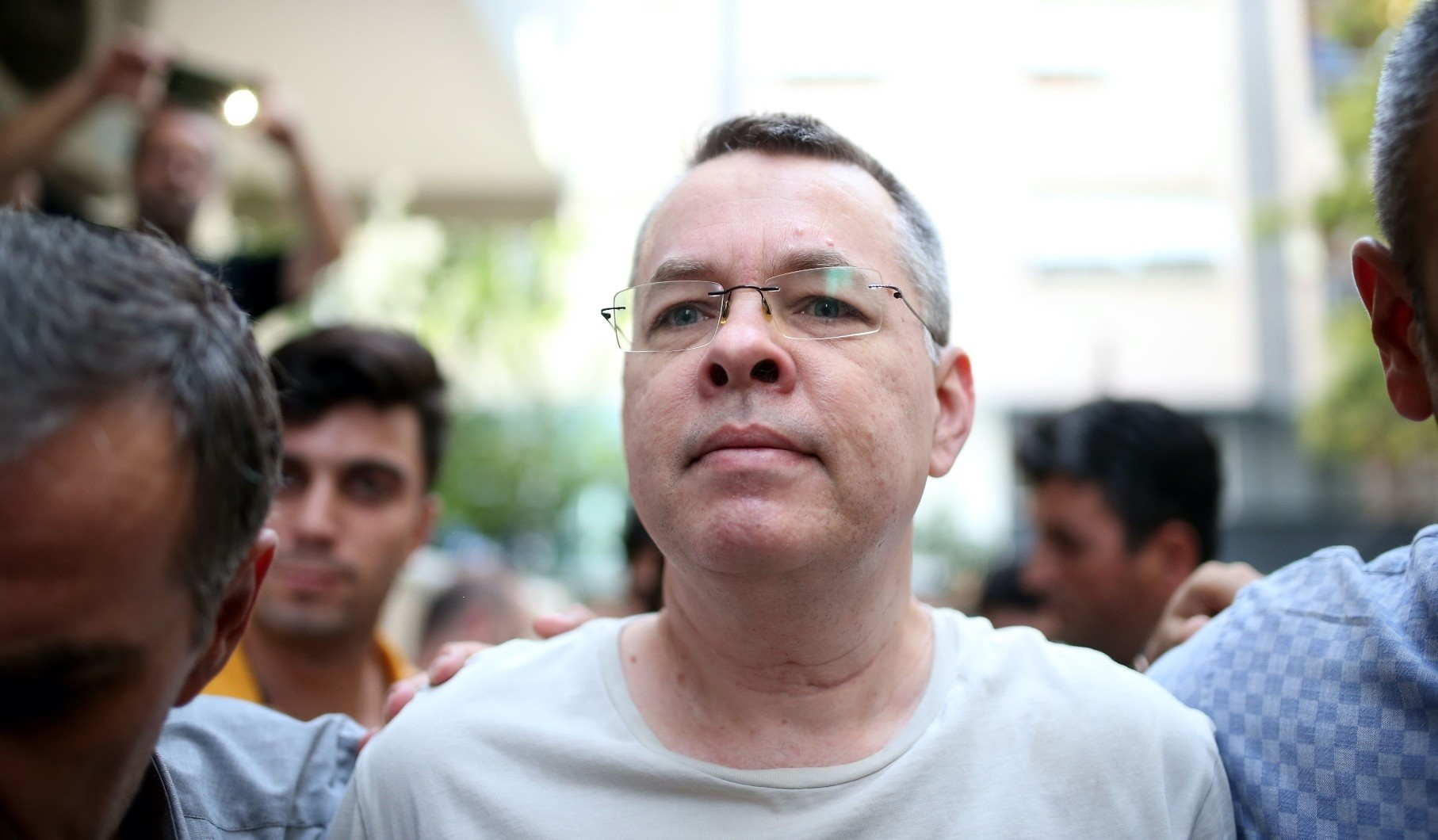 Pastor Andrew Craig Brunson is escorted by plainclothes police officers as he arrives at his house in Izmir, July 25.