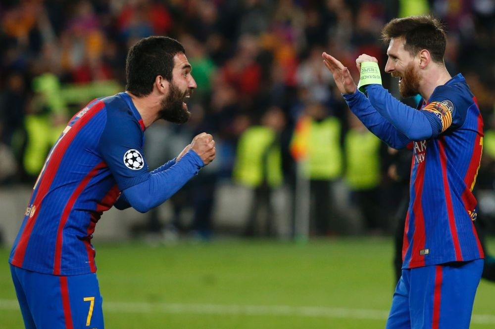 Barcelona's Argentinian forward Lionel Messi (R) celebrates with Barcelona's Turkish midfielder Arda Turan at the end of the UEFA Champions League round of 16 second leg football match FC Barcelona vs Paris Saint-Germain FC at the Camp Nou stadium.