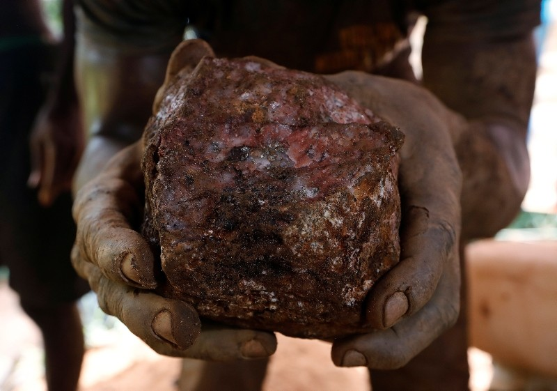 An artisanal miner holds up a rock containing gold that was removed from inside a mining pit at the unlicensed mining site of Nsuaem Top in Ghana, November 24, 2018.