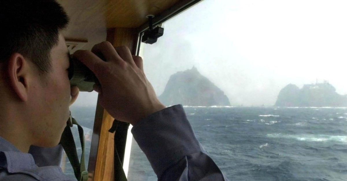 In this April 28, 2005, file photo, a South Korean coast guard looks at Dokdo islets, known as ,Takeshima, in Japanese, through a telescope on the patrol ship Sambong-ho on the East Sea, South Korea. (AP Photo)