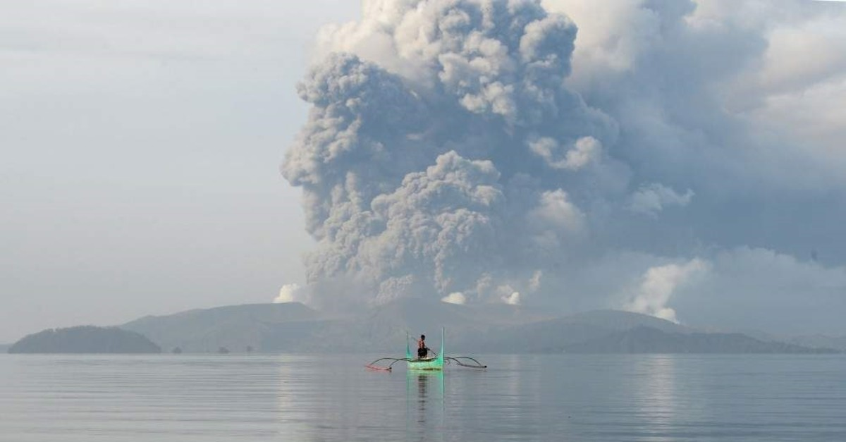 A youth living at the foot of Taal volcano rides an outrigger canoe while the volcano spews ash as seen from Tanauan town inBatangas province, Manila, Jan. 13, 2020. (AFP Photo)