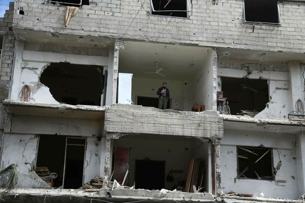 A Syrian man stands inside a damaged building in the opposition-held town of Hamouria, Eastern Ghouta, Feb. 27.