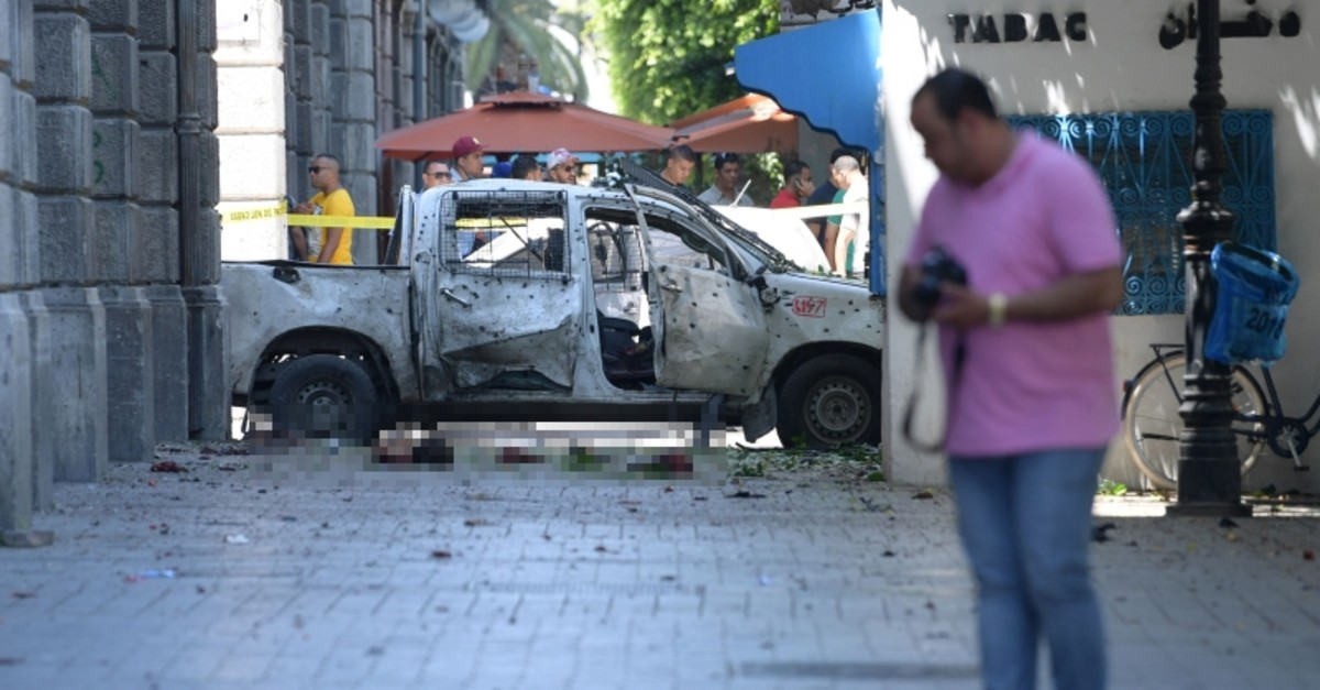 Body parts lie next to a shrapnel riddled vehicle at the site of attack in the Tunisian capital's main avenue Habib Bourguiba on June 27, 2019. (AFP Photo)