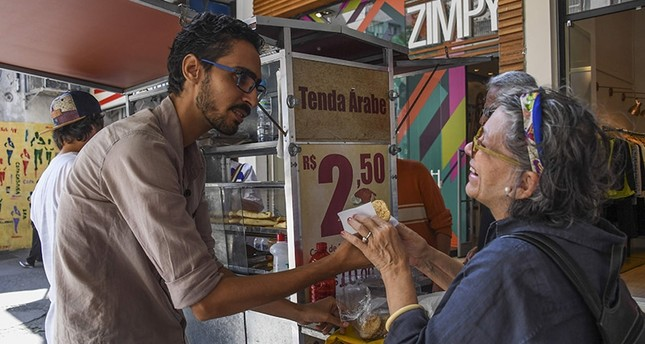 Egyptian immigrant Mohamed Ali Abdelmoatty Kenawy attends to a customer at his food stand in the Copacabana neighborhood in Rio de Janeiro on August 24, 2017. (AFP Photo)