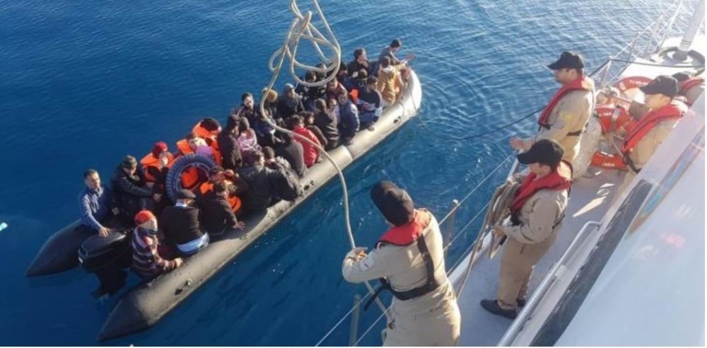 Turkish Coast Guard officials hurls a rope to a boat full of migrants in the Aegean Sea. Migrants pay large sums to smugglers for a spot in packed dinghies.