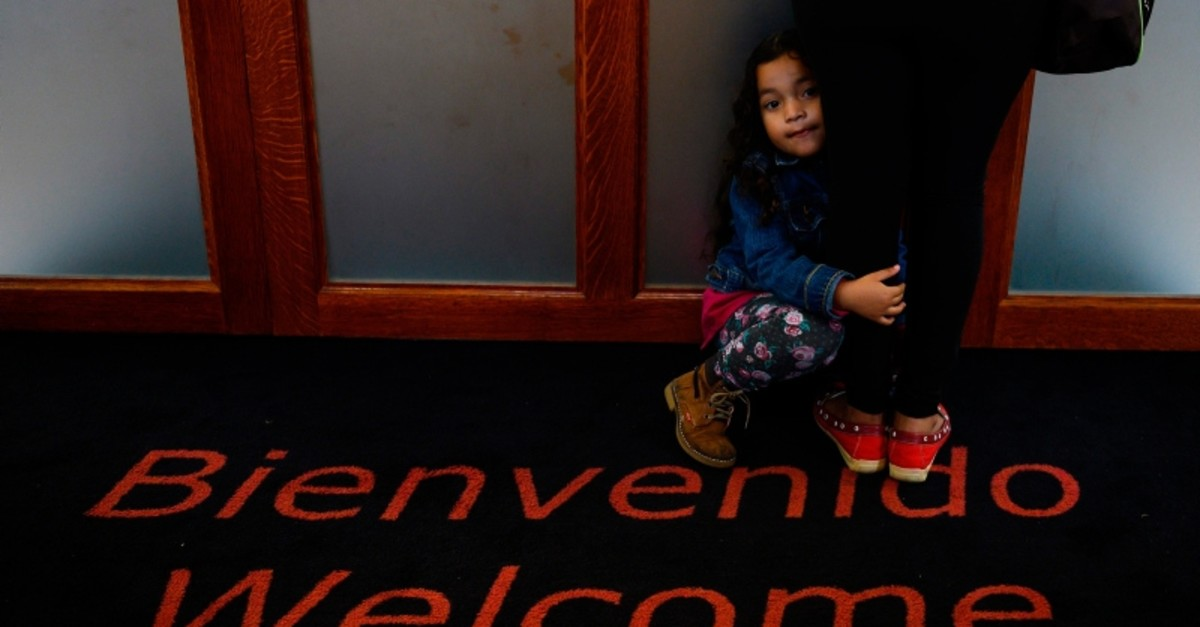 A young girl holds her mother's leg at the office of the immigrants rights group CASA in Langley Park, Maryland on Sept. 17, 2019. (AFP Photo)
