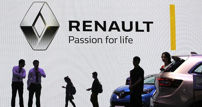 In this April 20, 2017 file photo, visitors walk past the Renault stand during the Auto Shanghai 2017 show at the National Exhibition and Convention Center in Shanghai, China. (AP Photo)
