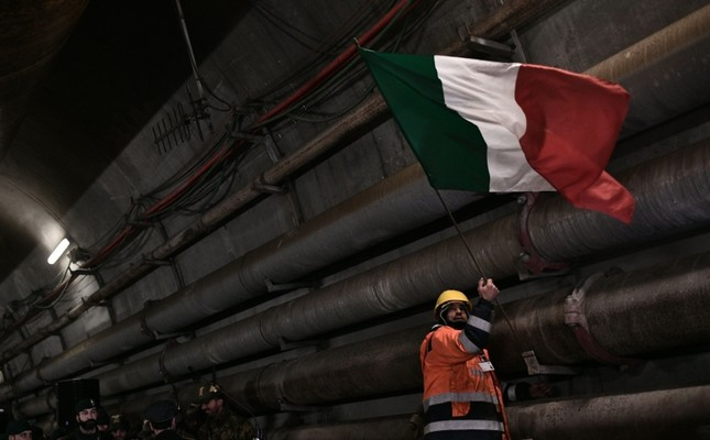 A worker puts up the Italian national flag during a visit of Italy's Interior Minister and deputy Prime Minister Matteo Salvini to the building site of a high-speed train line between Italy and France, Feb. 1, 2019 in Chiomonte, Italy. AFP Photo