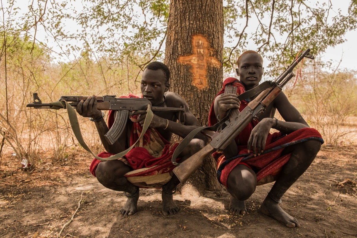 Cattle keepers Achiek Butich (left) and Makal Maker pose with their weapons, used to protect their herds in a nation where conflict has broken out in recent years.