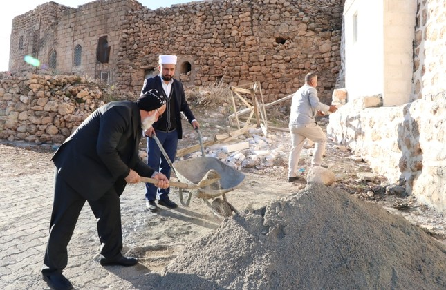 Rev. Savcı shovels sand into a cart carried by imam Kardaş.
