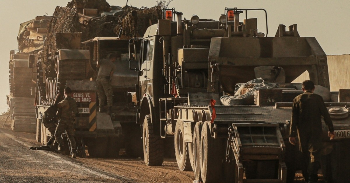 Turkish soldiers work on uploading tanks from trucks on a road towards the border of Syria in u015eanlu0131urfa province, Turkey, Monday, Oct. 14, 2019. (AP Photo)