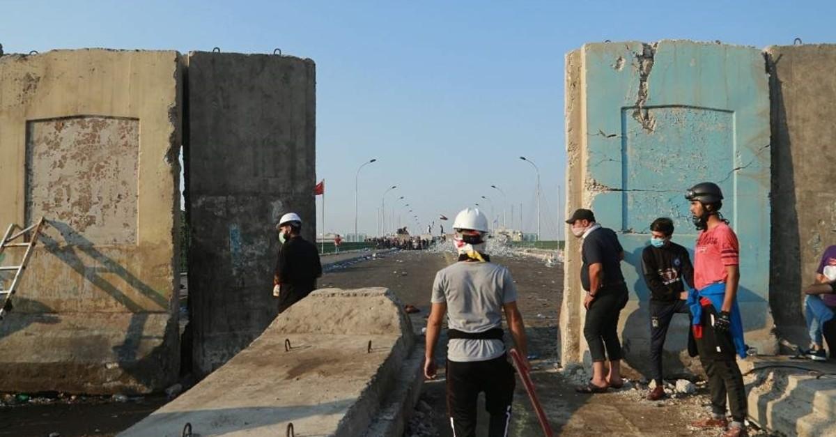 Anti-government protesters pull down concrete walls on Al-Sanak Bridge leading to the Green Zone, Baghdad, Oct. 31, 2019. (AP Photo)