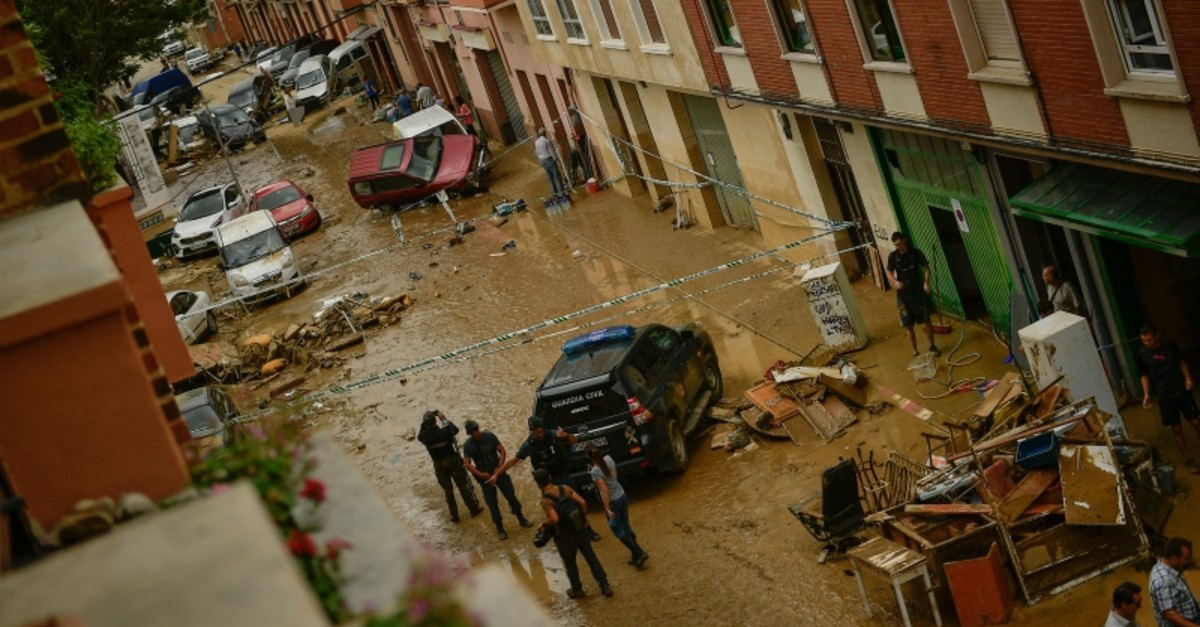 Residents gather in the street next to damaged cars after heavy rains in in Tafalla, northern Spain, Tuesday, July 9, 2019. (AP Photo)