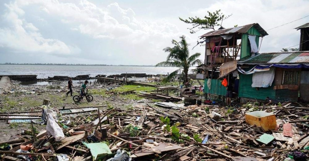 Residents walk past a house damaged during Typhoon Phanfone in Tacloban, Leyte province, central Philippines, Dec. 25, 2019. (AFP Photo)
