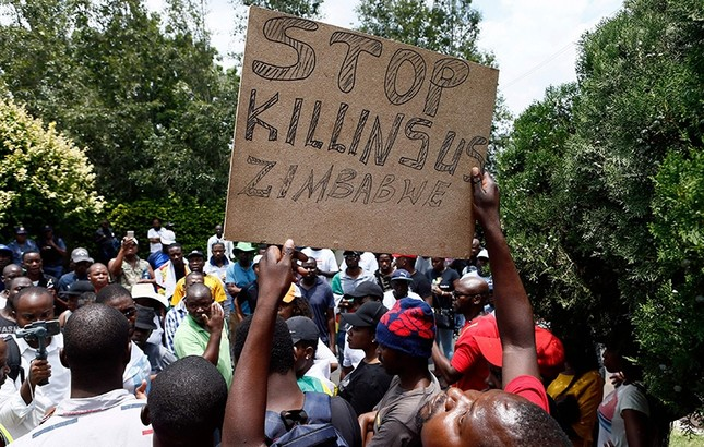 A protester holds a placard during a demonstration of Zimbabwean citizens outside the Zimbabwean Embassy in Pretoria  on Jan. 16, 2019. (AFP Photo)
