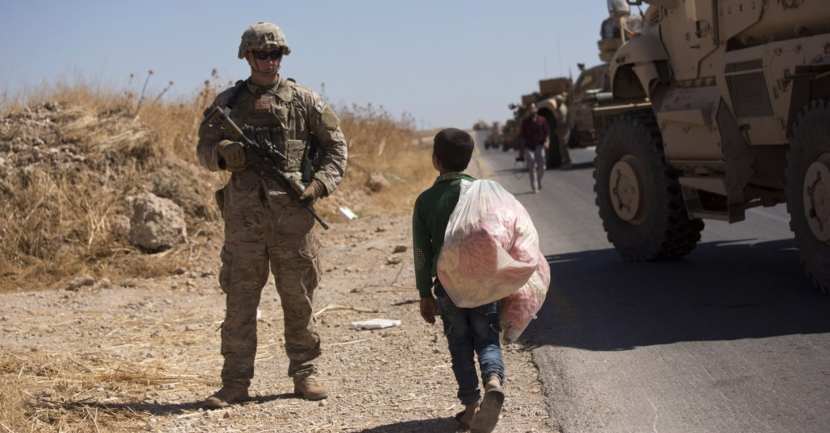 A Syrian boy selling snacks looks at a U.S. soldier standing guard during the first joint ground patrol by American and Turkish forces in the so-called ,safe zone, on the Syrian side of the border with Turkey, Sept. 8, 2019.