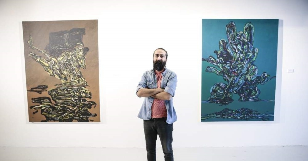 Adnan Jetto poses with some of his works at the exhibition. (AA Photo)