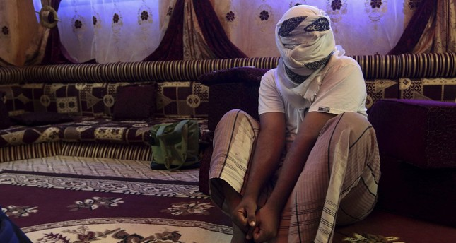 A former detainee covers his face for fear of being detained again, as he shows how he was kept in handcuffs and leg shackles while held in a secret prison at Riyan airport in the Yemeni city of Mukalla. (AP Photo)