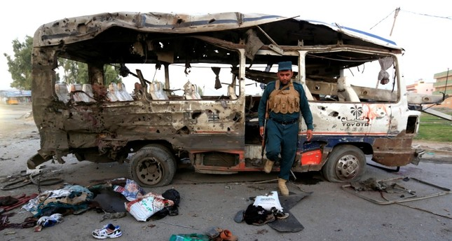 An Afghan policeman inspects a damaged minibus after a blast in Jalalabad, Afghanistan Oct. 7, 2019. (Reuters Photo)