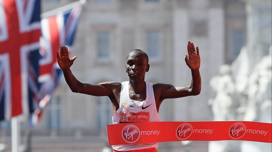 Kenyau2019s Eliud Kipchoge reacts after crossing the finish line to win the Menu2019s race in the London Marathon in central London.