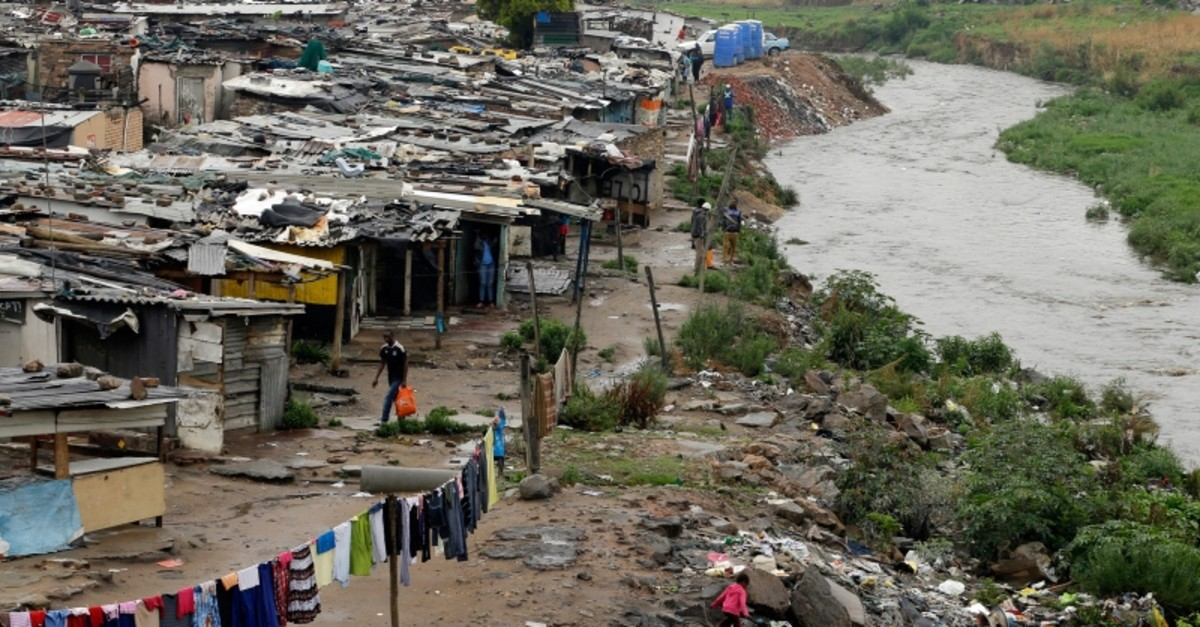 In this Nov. 11, 2014, file photo, a man walks along an informal settlement as a young girl plays next to the polluted Jukskei River in Alexandra, northern Johannesburg, South Africa (AP Photo)