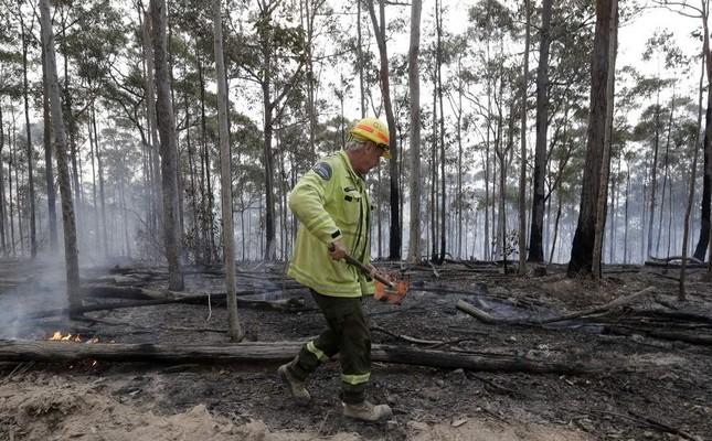 A worker patrols a controlled fire as they work on building a containment line for a wildfire near Bodalla, Jan. 12, 2020. AP Photo