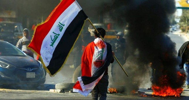 A demonstrator carries an Iraqi flag as he walks near burning tires during ongoing anti-government protests, Najaf, Jan. 12, 2020. Reuters Photo