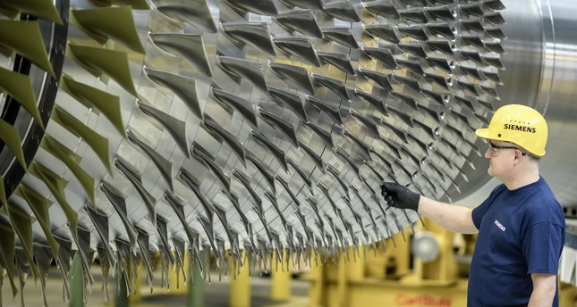 A worker poses on request of press photographers next to a turbine at the Siemens Gas Turbine Plant in Berlin, Germany, 02 March 2017. (EPA Photo)
