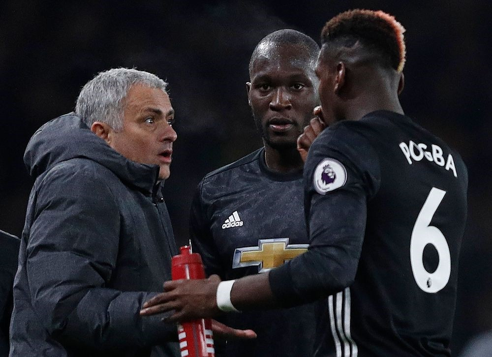 Manchester United's Portuguese manager Jose Mourinho (L) reacts as he talks with Romelu Lukaku (C) and Paul Pogba during the English Premier League match against Arsenal at the Emirates Stadium in London, Dec. 2, 2017.