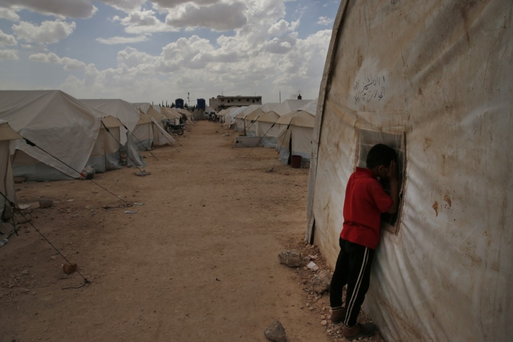 A Syrian child peeks inside a tent during leisure activities at a camp for internally displaced people in al-Bab, northern Syria, May 29.