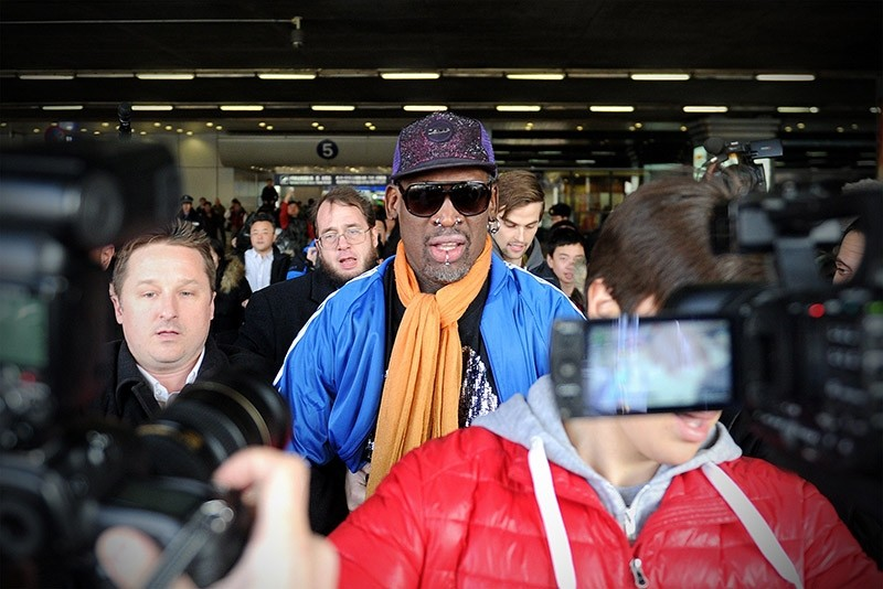 Former US basketball player Dennis Rodman (C) is surrounded by the media as he arrives at Beijing International Airport from North Korea on January 13, 2014 (AFP File Photo)