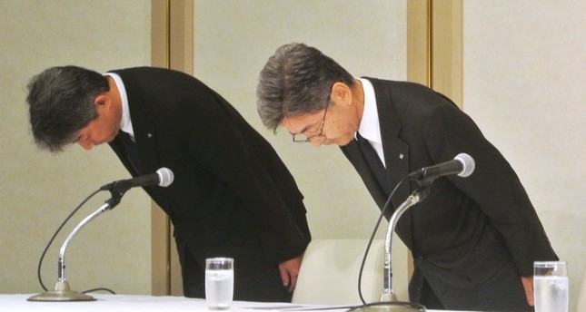 Kobe Steel's Executive Vice President Naoto Umehara (R) bows his head to apologize at a news conference in Tokyo.